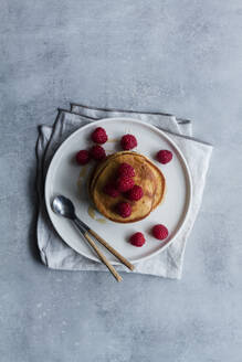 From above top view of tack of tasty pancakes with ripe raspberries placed on plate near spoons on gray background - ADSF13101