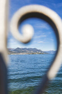Lake Maggiore seen through wrought iron fence on sunny day - FLMF00284