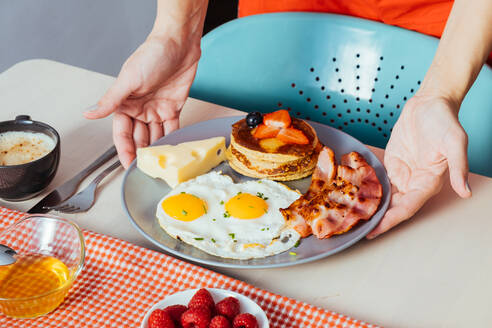 Anonymous crop hands putting plates with delicious fried eggs with bacon and cheese on table for breakfast - ADSF13166