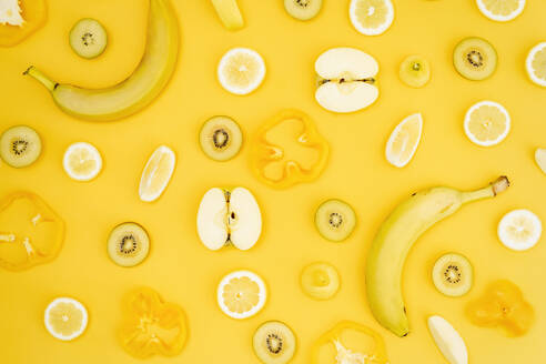 Top view of various fresh fruits and vegetables arranged on yellow background - ADSF13256