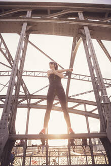 Woman stretching out arms on metal bridge at sunset - DHEF00329