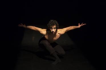 Male ballet dancer performing on black stage - NGF00614