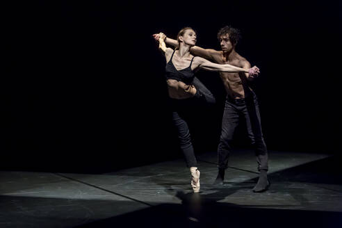 Male and femal dancer performing contemporary ballet on black stage - NGF00620