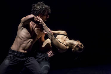 Male and femal dancer performing contemporary ballet on black stage - NGF00623