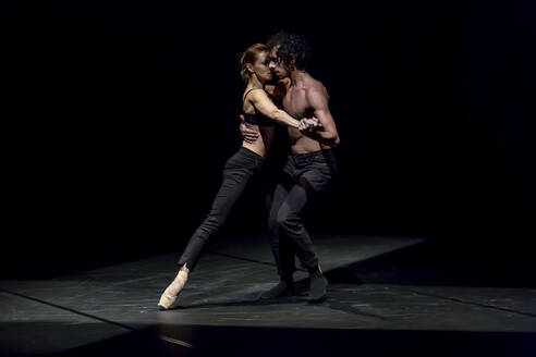 Male and femal dancer performing contemporary ballet on black stage - NGF00629