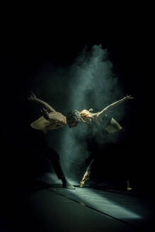 Male and femal dancer performing contemporary ballet on black stage - NGF00632