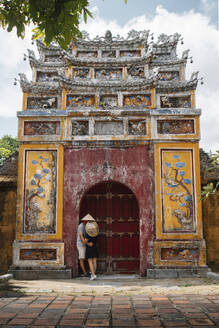 Back view of couple kissing below of towards shabby arch of Buddhist temple while sightseeing during vacation in Vietnam - ADSF13703