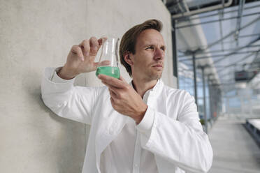 Scientist holding beaker with liquid at a wall - JOSEF01619