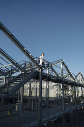Scientist on a metal construction under blue sky - JOSEF01622
