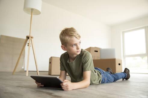 Boy using digital tablet looking away while lying on floor in new house - MJFKF00583