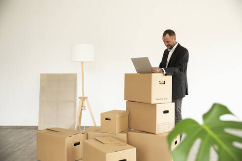 Businessman using laptop on cardboard box while standing in new unfurnished house - MJFKF00586