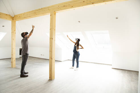 Couple looking through virtual reality simulators while standing in new attic - MJFKF00613