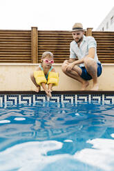 Little girl jumping into water, her uncle at poolside - JRFF04707