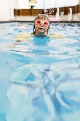 Little girl with swimming goggles in swimming pool - JRFF04713