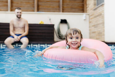 Little girl with floating tire and her uncle in swimming pool - JRFF04716