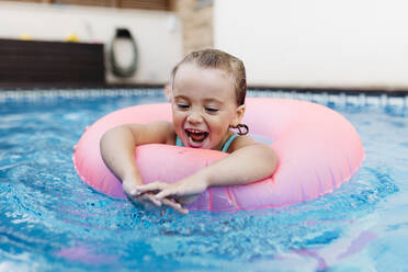 Portrait of little girl with floating tire in pool - JRFF04725