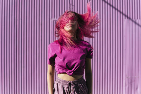 Young woman with dyed red hair dancing in front of purple wall in the city - TCEF00997
