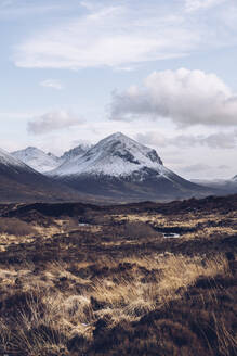 UK, Scotland, Brown grassy landscape of Isle of Skye in winter with snowcapped mountains in background - RSGF00274