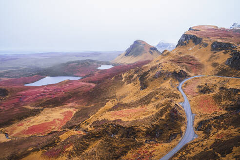 UK, Scotland, Drone view of empty highway stretching along brown mountainous landscape of Isle of Skye with small lakes in background - RSGF00280