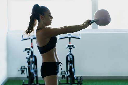 Side view of focused sportswoman in activewear standing in modern gym and doing kettlebell swings - ADSF13864