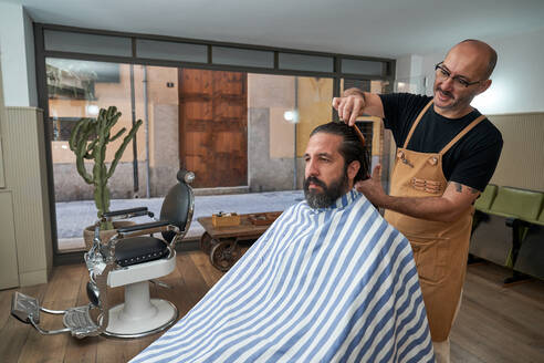 Barber combing hair while cutting hair to serious male customer in striped cape in modern barbershop with glass wall - ADSF14043