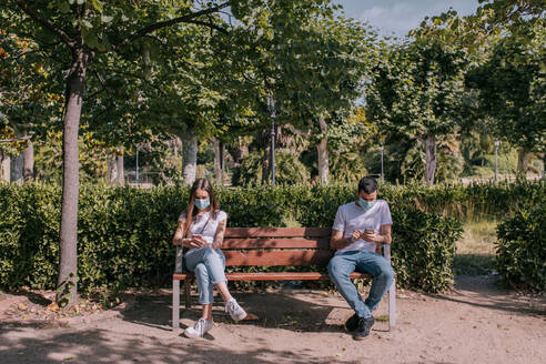 Couple at the park using the smartphone, wearing face masks and respecting social distancing during a pandemic - ADSF14127