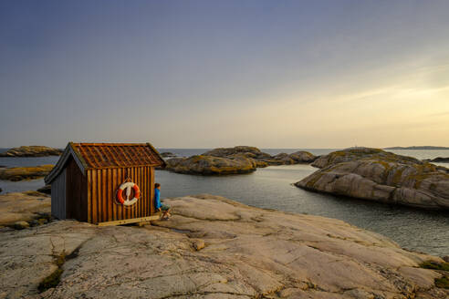Sweden, Vastra Gotaland County, Grebbestad, Man sitting on edge of coastal hut at Tjurpannans Nature Preserve - LBF03195