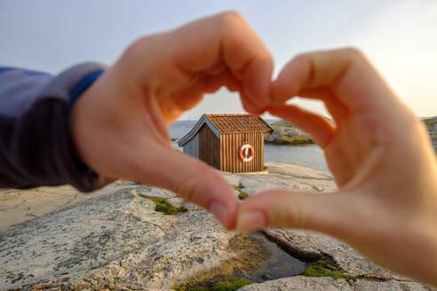 Sweden, Vastra Gotaland County, Grebbestad, Hands of girl making heart shape against hut on rocky shore of Tjurpannans Nature Preserve - LBF03198