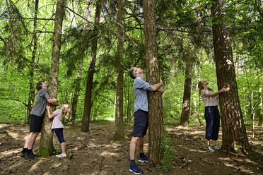 Parents and children embracing tree while standing in forest - ECPF01030