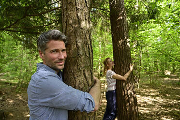 Smiling man and woman hugging tree while standing in forest - ECPF01033