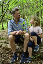 Father talking with daughter while sitting on log in forest - ECPF01036