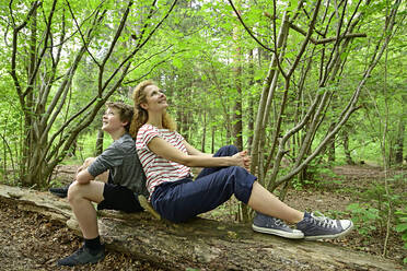 Thoughtful mother and son sitting back to back on fallen tree in forest - ECPF01039