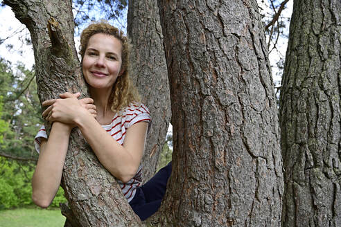 Smiling woman embracing while sitting on tree in forest - ECPF01042