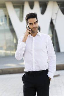 Confident businessman with hand in pocket talking over smart phone while standing in city - AFVF07153