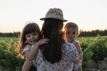 Mother and little daughters in a vineyard at sunset in Provence, France - GEMF04125