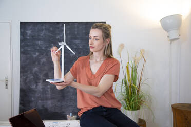 Woman in office holding wind turbine model - FKF03816