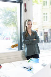 Portrait of woman leaning against glass door in office - FKF03837