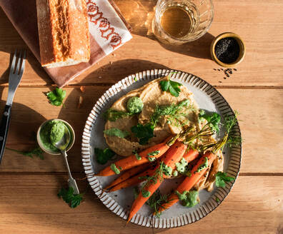 Top view of slices of fresh bread spread with hummus on plate with fresh orange carrots decorated with green sauce on wooden table - ADSF14287