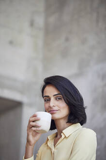 Close-up of confident businesswoman holding coffee cup against wall in office - MCF01244