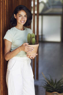 Smiling businesswoman holding cactus plant while standing by wall in office - MCF01265
