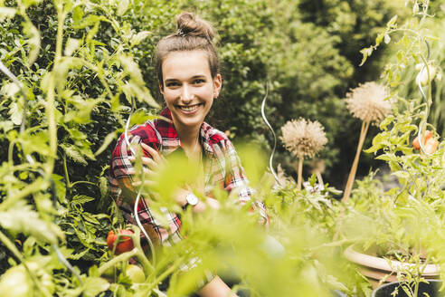 Smiling beautiful woman sitting amidst plants in vegetable garden - UUF21017