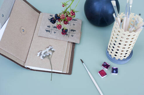Watercolor paints, dried flowers, note pad and DIY rattan desk organizer with paintbrushes - GISF00638