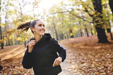 Young woman jogging in autumn forest - BSZF01685