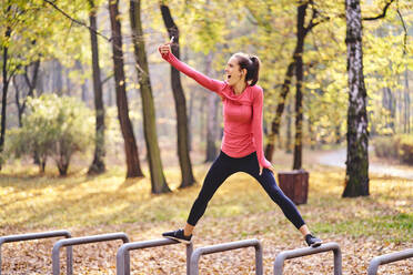 Young female jogger taking a selfie on bicycle stand in autumn forest - BSZF01691