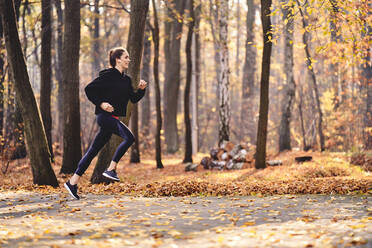 Young woman jogging in autumn forest - BSZF01697