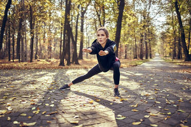 Young female jogger stretching her leg in autumn forest - BSZF01703