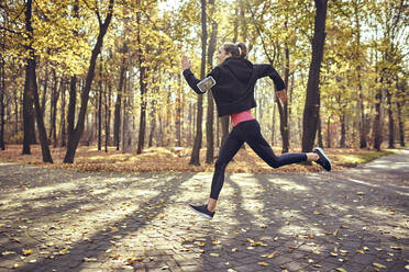 Young woman jogging in autumn forest - BSZF01706