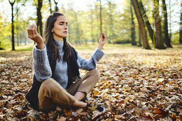 Young woman meditating in autumn forest - BSZF01712