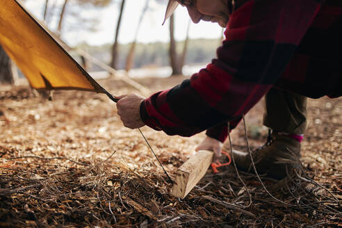 Midsection of bushcrafter preparing tent in forest - SASF00041