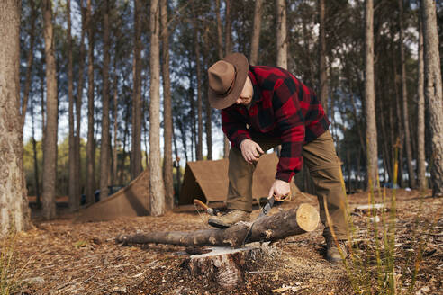 Buschcrafter cutting log with hand saw in forest - SASF00044